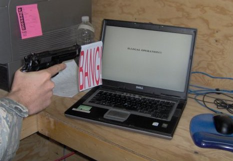 A gun pointed at a computer that says illegal operation.