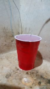 Cup with two wires hooked up, water running into the top, and water overflowing down the side.  Cup is sitting in a laundry room slop sink.