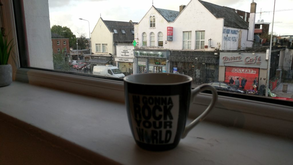 A cup of coffee on a windowsill looking out over a Dublin street