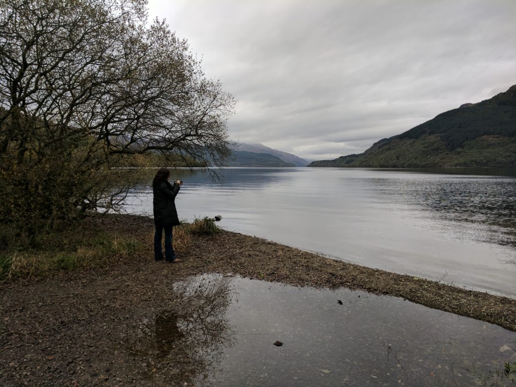 Sarah taking a photo at Loch Lomond, looking out over the large lake