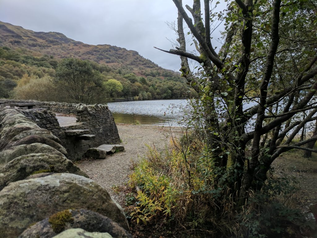 A stone wall and steps down to a beach area at Loch Lomond