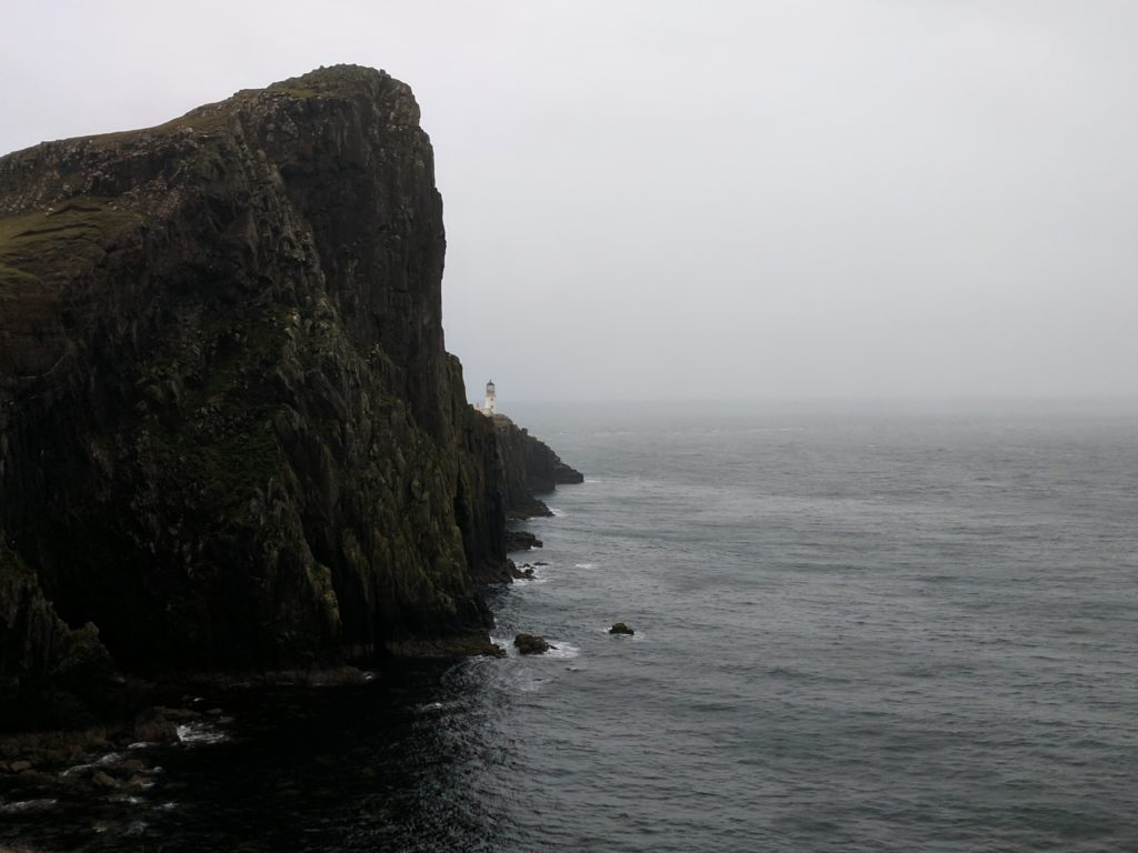 A large cliff in the foreground, and the lighthouse in the background, the Neist Point hike takes you past all of this